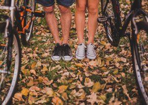 homme en converse noires et femme en converse blanches avec vélos feuilles automne